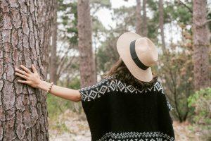 Woman touching tree trunk